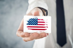 American Businessman holding business card with USA Flag. International cooperation, investments, business opportunites concept.